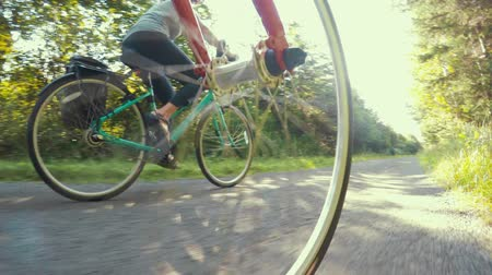 ciclismo : Fun shot of couple biking in a green forest on bike trail