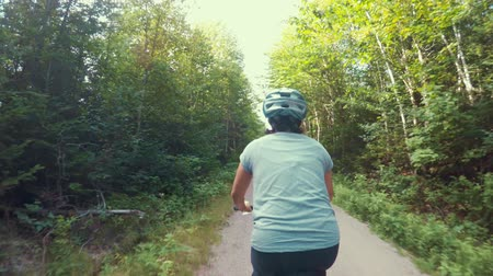 ciclismo : Fun shot of a woman biking in tall green forest on bike trail