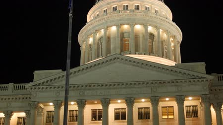burocracia : Lights on Utah State Capitol dome with flags tilting shot