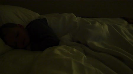 colchão : Little boy sleeping in a hotel bed at night dolly shot