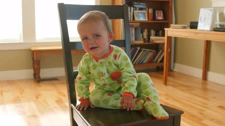 fegyelem : Little toddler cries after being put on time out chair Stock mozgókép