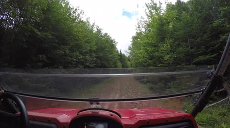 четыре человека : Low shot of a large four wheeler riding through grass and trees