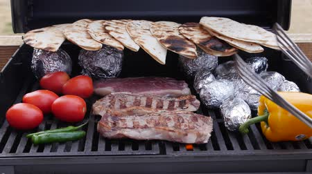tomate : Man cooks Mexican food on the barbecue grill outside for dinner