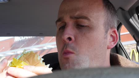 нездоровое питание : Man eating fast food in his car Стоковые видеозаписи