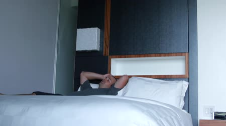ágynemű : Man relaxes in modern hotel on bed Stock mozgókép
