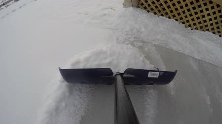 janeiro : Man shovels snow from off a driveway at his house