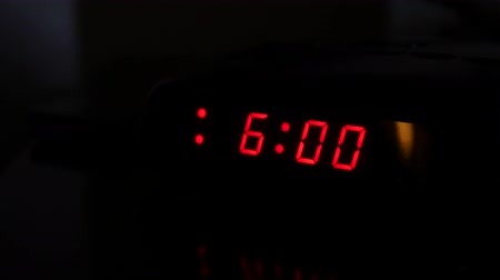 pm : Man turns off alarm clock and turns on light Stock Footage