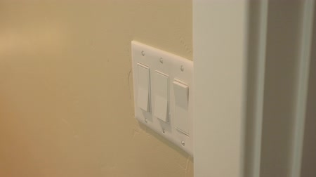 utilidade : Mans hand uses light switch to turn on and off light