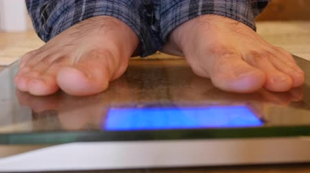 baixo teor de gordura : Mans feet step on scale to weigh himself