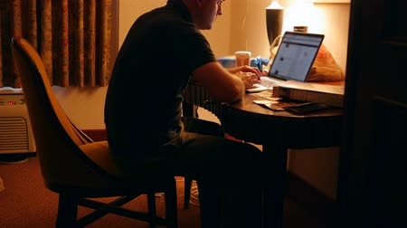 lampy : Man working in dark hotel room at night on computer