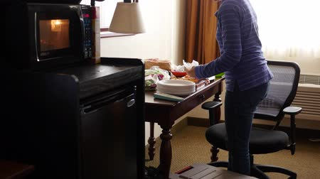 refrigerador : Mother cooking microwave pizzas for dinner in hotel