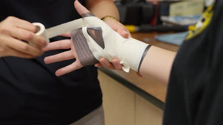 applying : Nurse tapes a girls sprained wrist at hospital