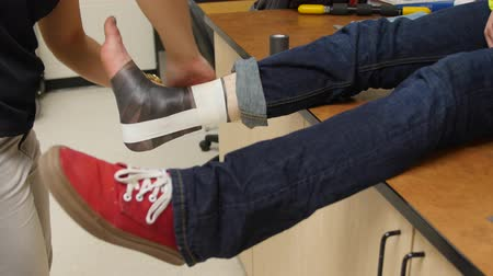 first aid kit : Nurse taping a boys sprained ankle Stock Footage