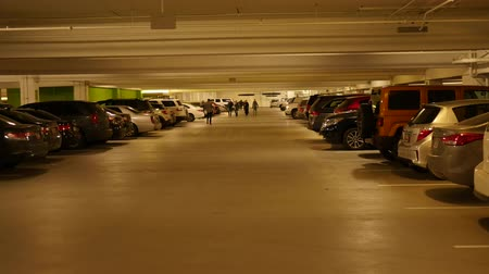 garagem : People in full underground parking garage with lots of cars