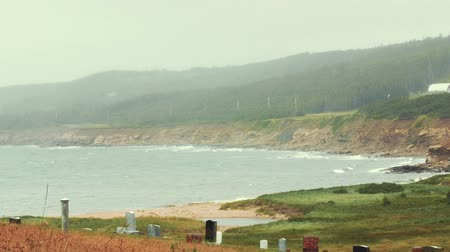 cape breton : Rain and rough ocean waves on a rocky coastline with cemetery Stock Footage