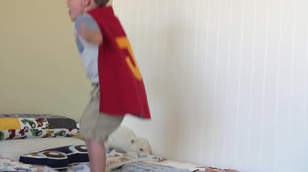 ágynemű : Slow motion a toddler with a cape jumps off his bed in room