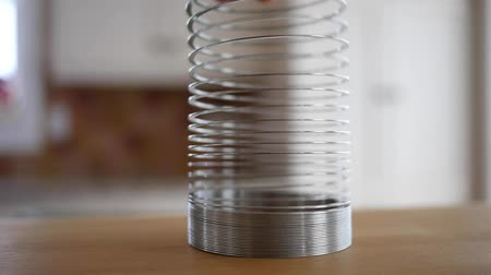 esneme : Slow motion of a mans hands play with a slinky Stok Video
