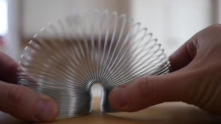 mértani : Slow motion of mans hands play with a slinky