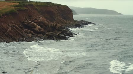 rekreasyon : Slow motion shot of a very rocky shore cliffs and the rough ocean water