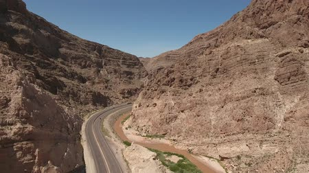 teherautó : Time lapse aerial shot cars driving through desert canyon by river