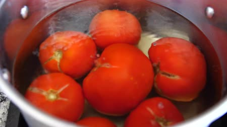 ocet : Tomatos boil for salsa in a pot of hot water