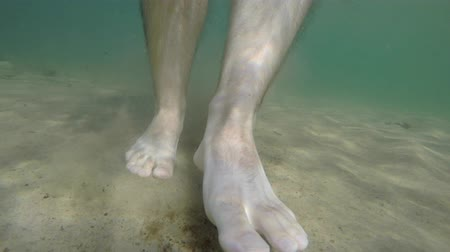 masculino : Underwater shot mans bare feet walking along ocean sandy beach