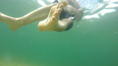 adam : Underwater shot of a man treading in the ocean on calm beach Stok Video