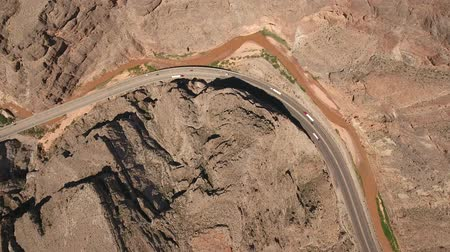 nevada : Very high aerial shot of cars driving in desert canyon by river Stock Footage