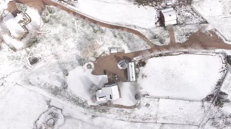 inferior : Very high aerial shot over a house and field in winter Vídeos