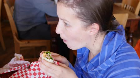 pastelaria : Woman eating her sandwich wrap in a sandwich shop Stock Footage