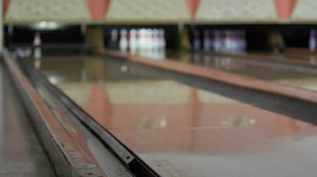 sorok : Woman hits pins with bowling ball in bowling alley