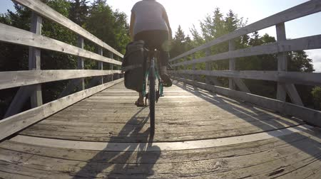 ciclismo : Woman on bike rides over tall wooden bridge