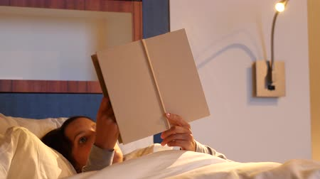 colchão : Woman reading a book in comfortable bed at hotel room Stock Footage
