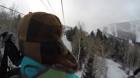 buty : Woman riding on ski lift on cold day
