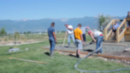 levelling : Workers levelling a freshly poured concrete patio out of focus