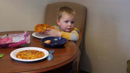 refrigerador : Young family eats microwave pizzas for dinner in hotel