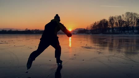 Slow-motion footage of hockey player skating on a frozen lake into the sunset in winter
