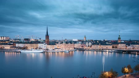 skandináv : Day to night time lapse motion footage of famous Stockholm city center with historic Riddarholmen in Gamla Stan old town district during blue hour at dusk, Sodermalm, central Stockholm, Sweden Stock mozgókép