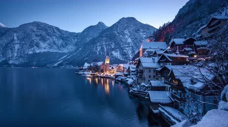 frozen lake : Day to night time-lapse of famous Hallstatt lakeside town embedded in beautiful winter wonderland scenery in the Alps during scenic Christmas time, Salzkammergut region, Austria Stock Footage