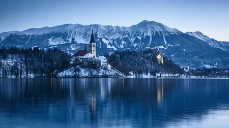 meseország : Night to day time-lapse footage of famous Bled Island (Blejski otok) at scenic Lake Bled with Bled Castle (Blejski grad) and Julian Alps in the background on a beautiful sunny day in winter, Slovenia