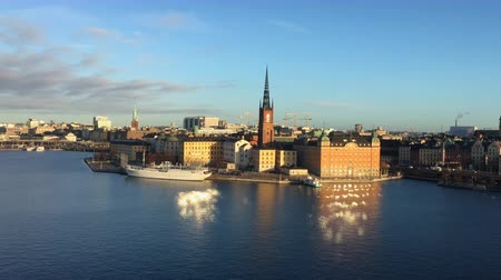 Скандинавия : Stockholm city center with historic Riddarholmen in Gamla Stan old town district in beautiful morning light at sunrise with blue sky and clouds, central Stockholm, Sweden Стоковые видеозаписи