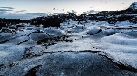 congelado : Frozen rock pools and seaweed in panning winter coastal scene from Norway