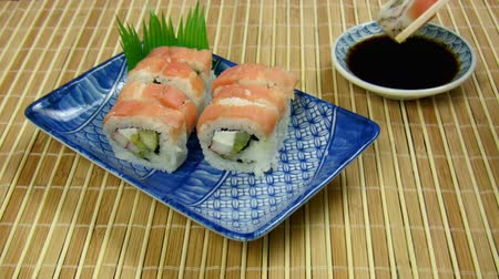 cozinha japonesa : Salmon Sushi Roll Eaten (HD). A delicious Salmon Sushi roll eaten quickly after tray is placed. Used a higher speed to show the rapid eating.  Stock Footage