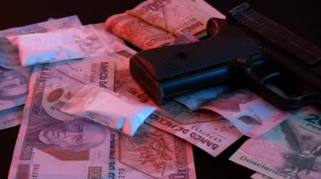 kokaina : Mexican Drug Bust Pan Right (HD). This shot shows a gun with Mexican money scattered and a few bags of cocaine in bags. Shot to the right.