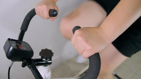 ciclismo : Spinning exercise bike with female pedaling seen in a sequence of shots from various angles. Stock Footage