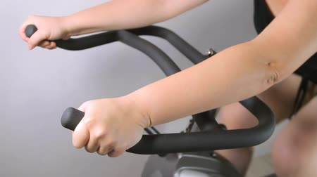 dizi : Exercise bike with female pedaling seen in a sequence of shots from various angles.