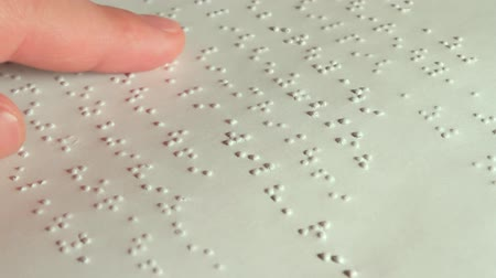 wzrok : Male Hand Reading Braille. Male hand reading braille dot language for the Blind.