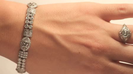 браслет : Vintage Diamond Jewelry (HD). Female hand with vintage Diamond bracelet and ring shot with special star glow filter for extra glare streaks. This are unbranded 80  year old jewelry pieces. Стоковые видеозаписи