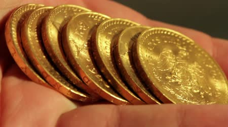 treasure : Gold Coins On Hand (HD). Pure gold bullion coins. These are called Centenario 50 gold peso coins 1945 vintage. Ambient audio included.