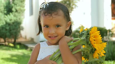 подсолнухи : Hispanic Girl Holding Sunflowers (HD). Hispanic four year old girl holding sunflowers happily after they are handed to her.